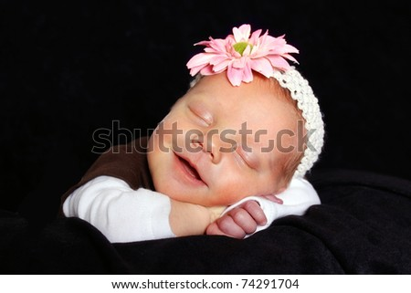 beautiful sleeping baby girl with a smile on her face - stock photo