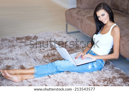 Beautiful slender woman relaxing with her laptop computer on her lap as she sits stretched out on the carpet in the living room in her bare feet smiling at the camera - stock photo