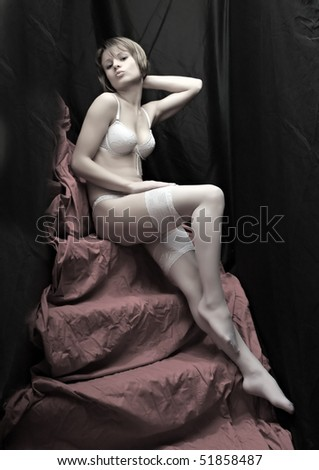 Beautiful slenderness young girl in white nylons on pink background. Vintage style low key studio shot. Great for calendar. - stock photo