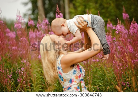 Beautiful slim blonde mom throws up and kisses adorable smiling baby boy on the background of grass fireweed in the summer - stock photo