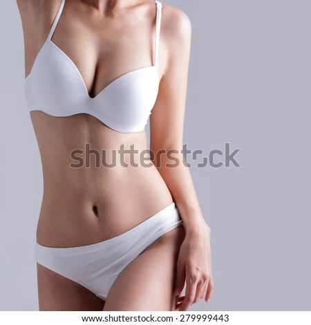 Beautiful slim body of woman isolated on gray background - stock photo