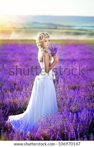 beautiful slim bride in luxurious wedding dress in purple lavender flowers. Fashion romantic stylish happy woman with blond hair. Smiling girl in sunset over summer lavenda waiting for groom -Provence - stock photo