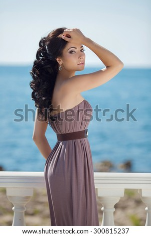 Beautiful slim brunette girl model posing in fashion dress by the sea, outdoor portrait  - stock photo