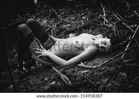 Beautiful slim brunette topless in a panties, garter belt and high stockings lying on a ground, in a forest, in a nature, glamour and nude photography, nudity, black and white photo - stock photo
