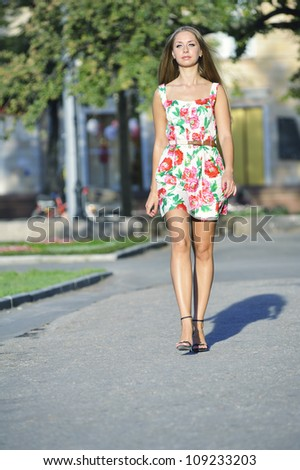 Beautiful slim girl in a bright dress walking down the street - stock photo