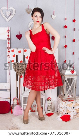 Beautiful slim girl in the red dress openwork. Young sexy model in a red dress with slim long legs standing on a bright background of hearts. - stock photo