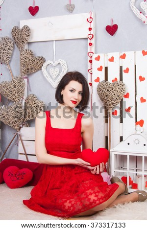 Beautiful slim girl in the red dress openwork. Young sexy model with red lips and red dress sitting on the pale. A girl holding a red heart - stock photo