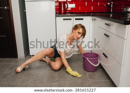 Beautiful slim sexy girl in the kitchen washing the floor - stock photo