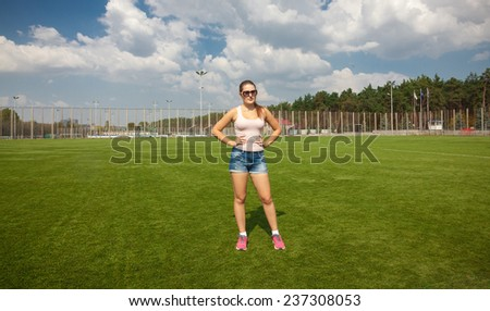 Beautiful slim woman standing on soccer field at sunny day - stock photo