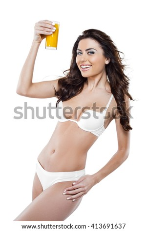 Beautiful slim woman wearing white lingerie. Studio shot of young seductive woman isolated on white background. Woman smiling and holding glass of orange juice - stock photo
