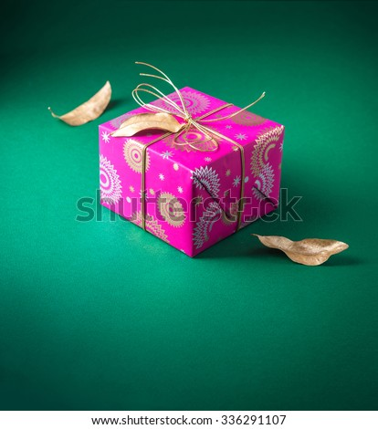 Beautiful small gift box wrapped with bright pink wrapping paper and arranged with dry golden leaves. Festive object and background. - stock photo