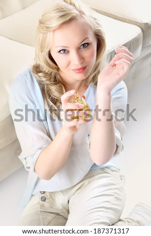 Beautiful smell- woman test perfume on her wrist. Form of a beautiful blonde holding in his hand a bottle of perfume  - stock photo