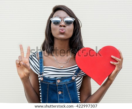 Beautiful smiling african woman holding a red heart. Fashion portrait stylish pretty woman in sunglasses outdoor. - stock photo