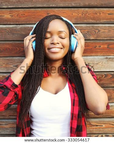 Beautiful smiling african woman with headphones enjoying listens to music in city - stock photo
