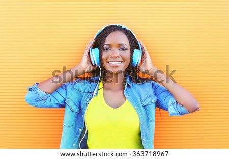 Beautiful smiling african woman with headphones enjoying listens to music over orange background - stock photo