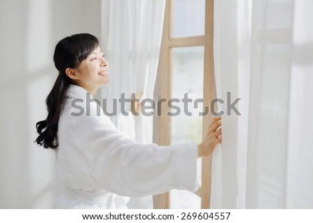 Beautiful smiling asian woman dressed in white bathrobe - stock photo