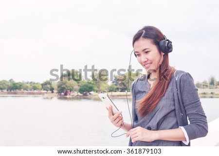 Beautiful smiling asian woman with headphones enjoying listens to music - stock photo