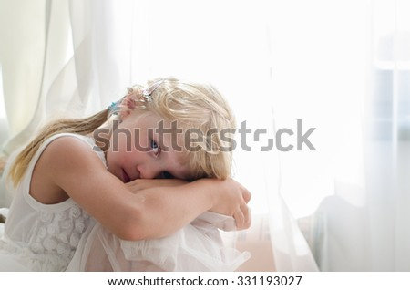 beautiful smiling blond girl sitting by the curtain - stock photo