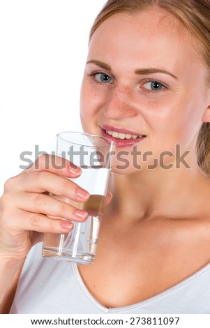 Beautiful smiling blonde girl holding a glass of water. A young athletic woman holding a transparent glass with water - stock photo
