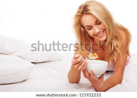 Beautiful smiling blonde woman eating a bowl of cereal lying on her stomach on her bed with copyspace - stock photo