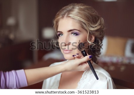 Beautiful smiling bride wedding with makeup and hairstyle. Stylist makes make-up bride on wedding day. portrait of young woman at morning. - stock photo