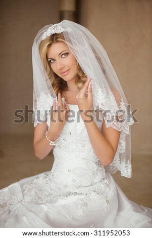 Beautiful smiling bride woman in wedding dress and bridal veil posing in interior. Beauty indoor portrait. - stock photo