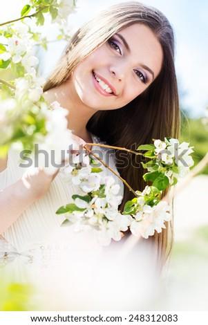 Beautiful smiling brunette girl near blossom cherry tree in spring garden - stock photo