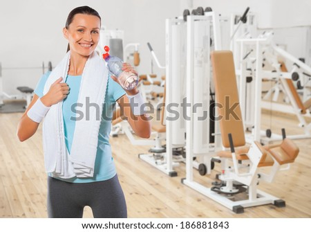 beautiful smiling brunette wearing sports clothes drinking  water from bottle - stock photo
