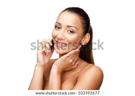 Beautiful smiling brunette woman with bare shoulders talking on her mobile phone isolated on white - stock photo