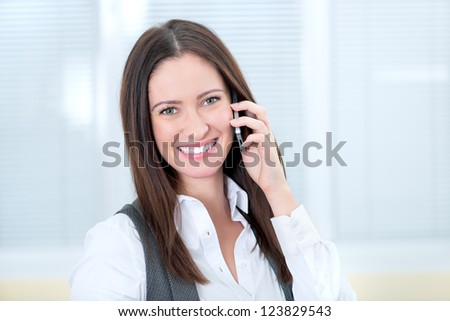 Beautiful smiling business lady speaks on a mobile phone. - stock photo