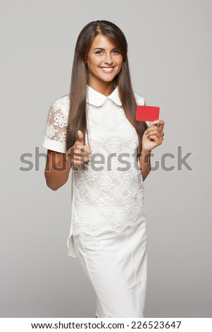 Beautiful smiling business woman showing red card in hand and gesturing thumb up, over gray background - stock photo