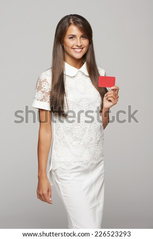Beautiful smiling business woman showing red card in hand, over gray background - stock photo
