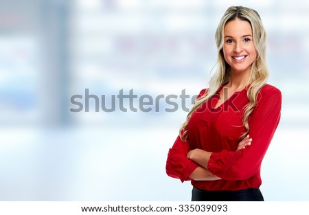 Beautiful smiling business womanover blue office background - stock photo