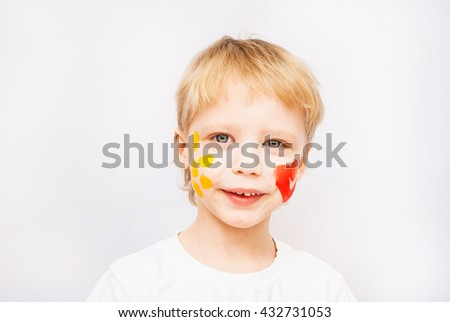 Beautiful smiling child face. Portrait of laughing emotional kid. Close up of cheerful funny boy isolated on white background. Baby with red heart and yellow sun on cheeks. Positive human emotions. - stock photo
