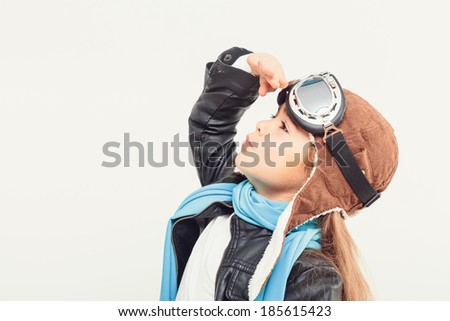 Beautiful smiling child (kid, girl) in helmet on a white background playing with a plane. Vintage pilot (aviator) concept - stock photo