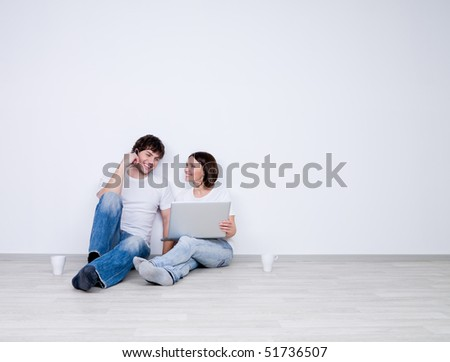 Beautiful smiling couple relax in the empty room with laptop  - new home - stock photo