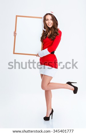 Beautiful smiling curly young girl in red santa claus costume with hood and shoes with high heels holding blank board over white background - stock photo