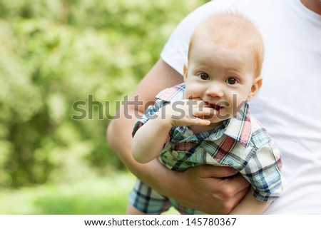 Beautiful smiling cute baby on father's hands - stock photo