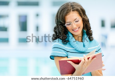 Beautiful smiling dark-haired woman in blue sweater and glasses reads interesting red book against spacious hall. - stock photo