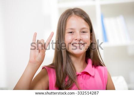 Beautiful smiling deaf girl using sign language - stock photo