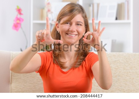 Beautiful smiling deaf woman using sign language showing L and O letters as a part of love word - stock photo