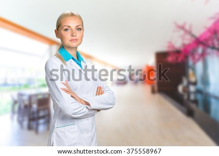 Beautiful smiling doctor woman in medical gown - stock photo