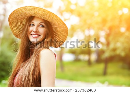 beautiful smiling dreaming woman in a hat in a summer park - stock photo