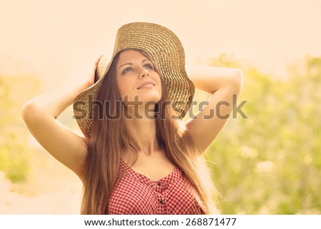 beautiful smiling dreaming woman in a hat in a summer park. toning effect - stock photo