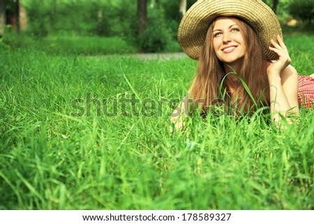 beautiful smiling dreaming woman in a hat lying on the grass in the summer sun - stock photo
