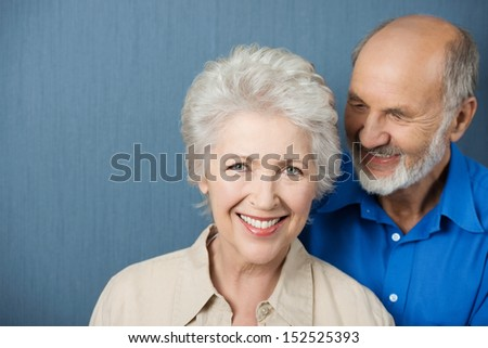 Beautiful smiling elderly woman looking at the camera with her husband standing alongside - stock photo