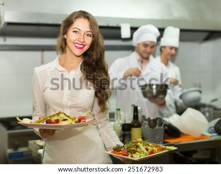 Beautiful smiling female waiter taking dish from kitchen in cafe - stock photo