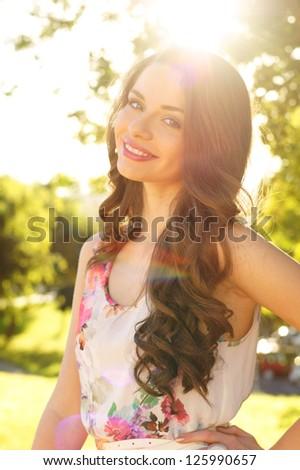 beautiful smiling girl against spring green bokeh background - stock photo