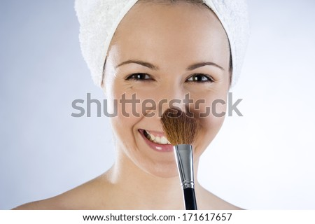 Beautiful smiling girl applying makeup - stock photo