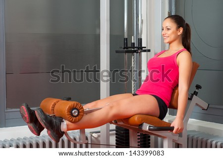 Beautiful smiling girl exercising legs on device in the health club. - stock photo